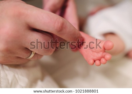 A father strokes a newborn baby's heel with a finger