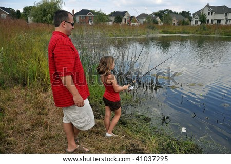 a father teaches his daughter to fish - stock photo