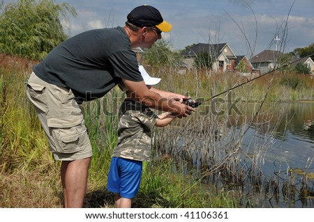 a father teaches his son to fish - stock photo