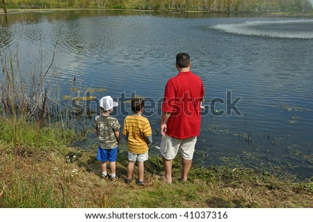 a father teaches his sons to fish - stock photo
