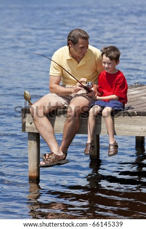 A father teaching his son fishing and catching a fish on a jetty outside in summer sunshine - stock photo