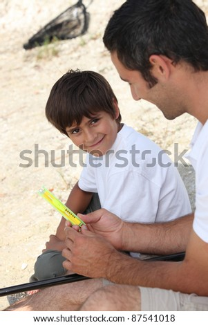 A father teaching his son how to fish.