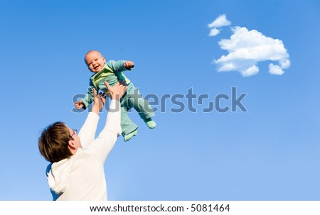 A father throwing his son in the air and catching him - stock photo