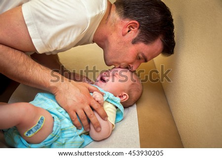 A father tries to comfort his 2 month old son with a kiss after the boy received his vaccination shots. - stock photo
