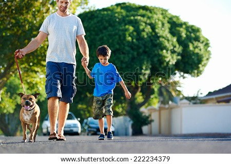 A father walking with his dog and his son in the suburbs - stock photo
