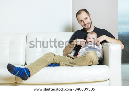 A father with baby on the sofa taking good time