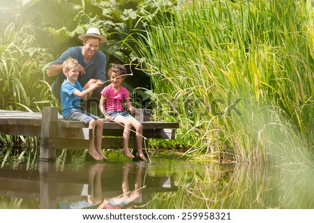 a father with his son and daughter engaged in fishing in a river, they are sitting on a wood pontoon - stock photo