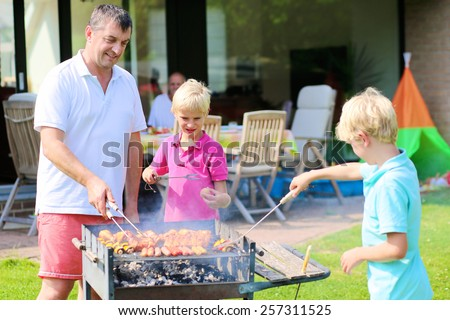 A father with sons, two twin teenage boys cooking meat on barbecue for summer family dinner at the backyard of the house - stock photo