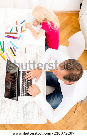 A father working on a laptop computer while his daughter is drawing.  - stock photo