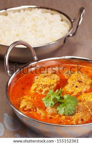 A favourite Indian curry, lamb rogan josh, garnished with coriander, in a balti dish with basmati rice in the background. - stock photo
