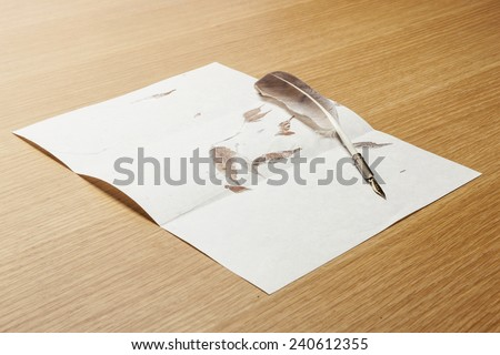 A feather quill pen with the letter paper(leaf) and wood desk(table) at the studio. - stock photo