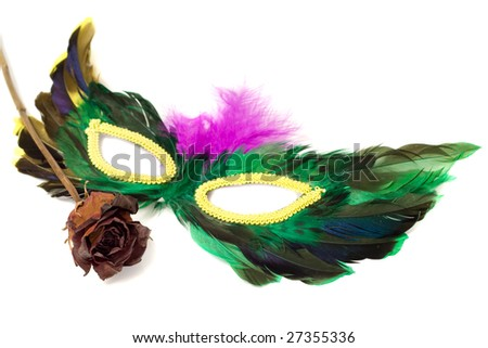 A feathered masquerade mask with a dried red rose, isolated against a white background