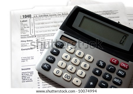 a federal tax form with a calculator sitting on top - stock photo