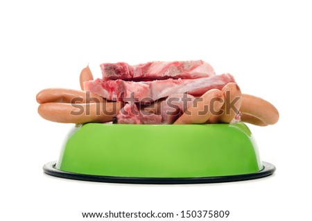 a feeding bowl full of meat and sausage before white background - stock photo