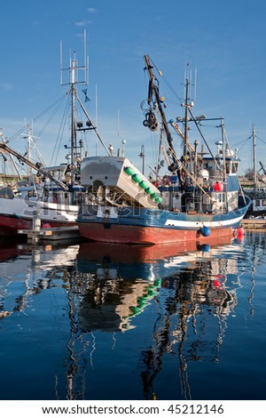 A feet of fishing boats by a dock - stock photo