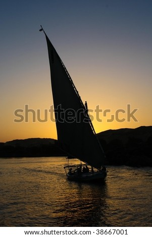 a feluka sailing boat on the nile river in egypt at sundown