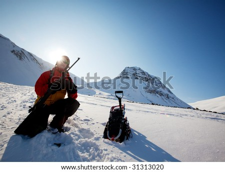 A female adventure loading a rifle as a safety precaution, Svalbard, Norway - stock photo