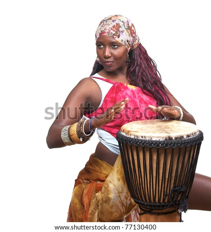 A female african musician plays the djembe drum.  She is isolated against a white background. - stock photo