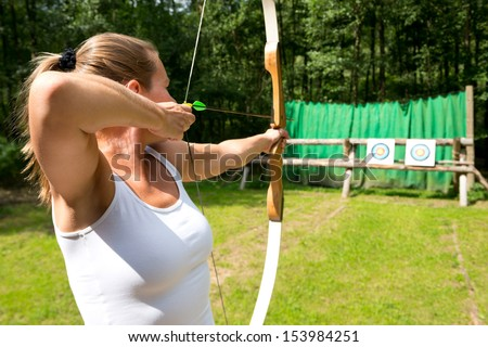 A female archer aiming at a target on a sunny day - stock photo