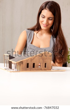 A female architect building a rough house study model - stock photo
