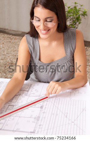 A female architect checking over blueprints, measuring with a scaled ruler - stock photo