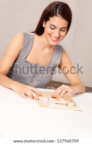 A female architect designing a scale model house - stock photo