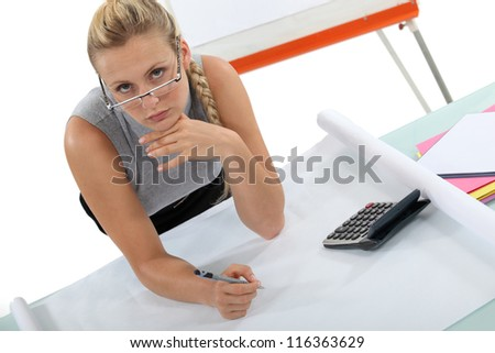 A female architect drawing plans. - stock photo
