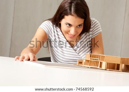 A female architect examining a rough model house - stock photo