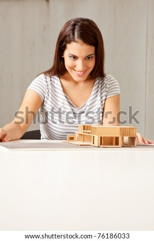 A female architect examining a rough model of a house - stock photo