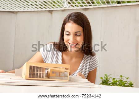 A female architect looking at a model house - stock photo