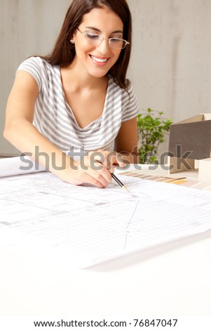 A female architect looking blueprints in an office - stock photo