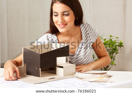 A female architect looking over a model house with blueprints and color swatches on the table - stock photo