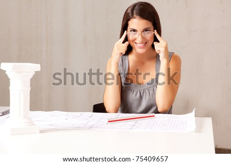 A female architect sitting at a desk with blue prints - room for copy space - stock photo