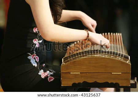 A female artist playing the Guzheng, a traditional chinese musical instrument at a Chinese New Year celebration. - stock photo