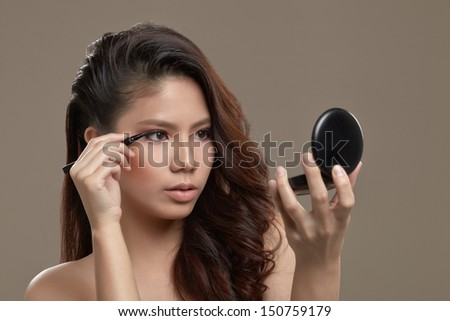A female asian with make up and pink eye shadow holding a liquid eye liner pen applying eye liner while looking at a mirror - stock photo