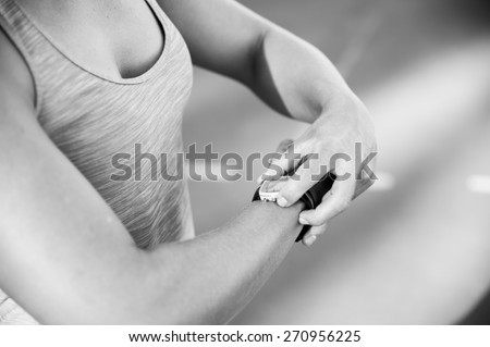 A female athlete at a running track adjusts her heart rate monitor before a workout - stock photo