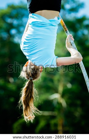 A female athlete competing in the pole vault at a track and field event - stock photo