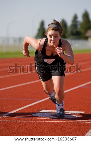A female athlete launching off the start line in race - stock photo