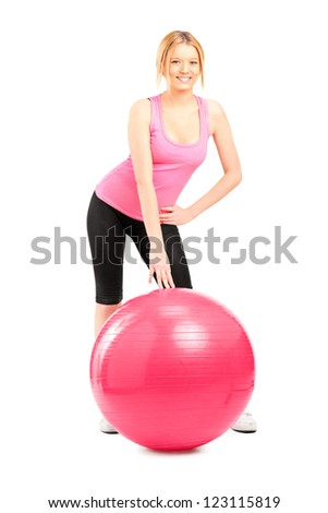 A female athlete posing next to a pilates ball isolated on white background