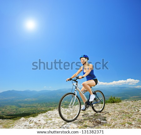 A female biker biking a mountain bike outdoors - stock photo