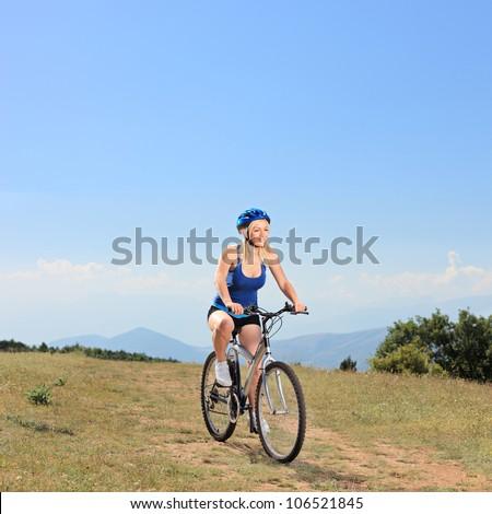A female biker riding a mountain bike outdoors - stock photo