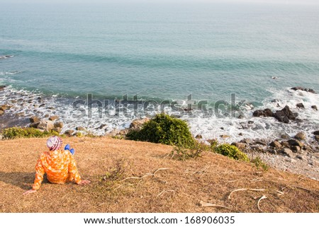 A female camping and looking at the sea - stock photo