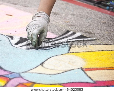 a female chalk artist working on a design - stock photo