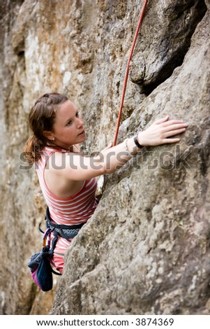 A female climber, climbing using a top rope on a steep rock face (crag).  A shallow depth of field has been used to isolated the climber, with the focus on the head and eyes.