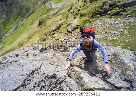 A female climber scrambling up Cam Ridge in Langstrath valley leading to the summit of Glaramara in the Lake District.
