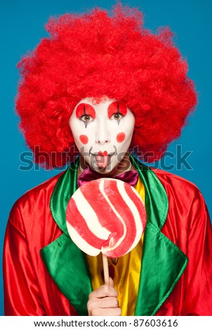 a female clown with colorful clothes and makeup holding a lolipop - stock photo