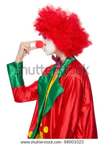 a female clown with colorful clothes and makeup squeezing her nose - stock photo