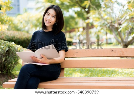 A female college student reading a book while lying on the park
