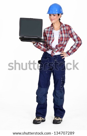 A female construction worker holding  a laptop. - stock photo