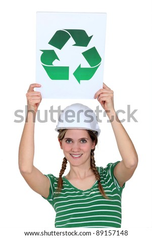 A female construction worker holding a recycling sign.